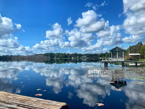 panoramic view of lake and houses against sky - julie culy stock pictures, royalty-free photos & images