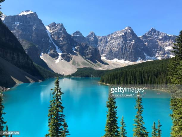 panoramic view of lake and mountains against clear blue sky - lake louise stock photos and pictures