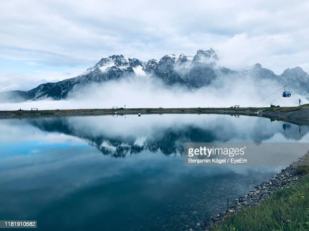panoramic view of lake and mountains against sky - leogang stock pictures, royalty-free photos & images