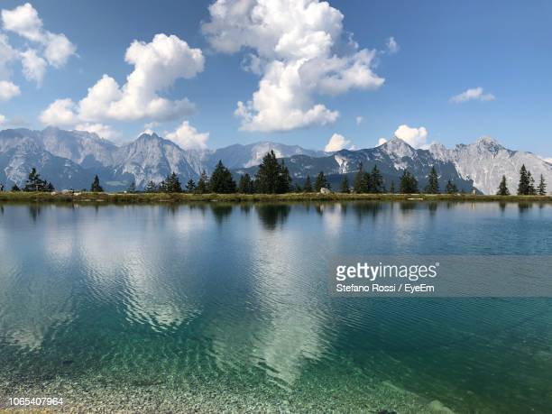 panoramic view of lake by mountains against sky - ゼーフェルト ストックフォトと画像