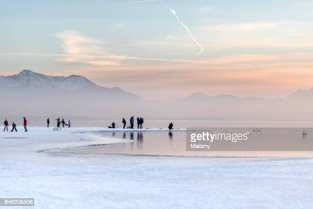Panoramic view of Lake Chiemsee in winter with people on the ice - Chiemsee, Bavaria, Germany
