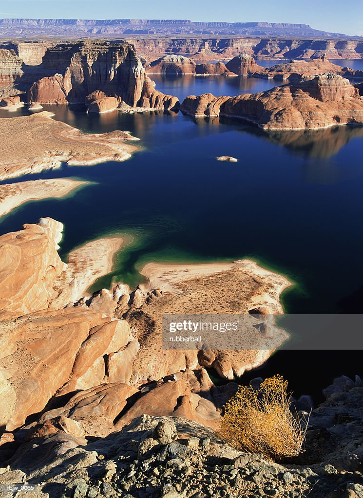 panoramic view of lake powell near page arizona with red rock formations in the distance and the dark blue water showing the contour of the canyons : Stockfoto