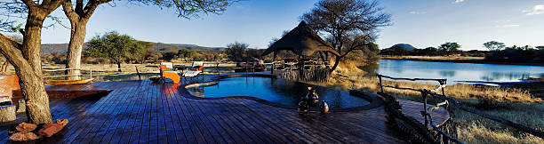 Panoramic view of lapa and swimming pool over a waterhole at Okonjima Private Game Reserve, Namibia. Part of the luxurious recreational areas offered at the Villa. (Digital Composite) (PR: Property Released)