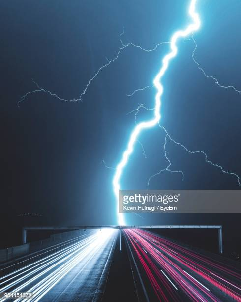 panoramic view of lightning over road - power in nature stock pictures, royalty-free photos & images