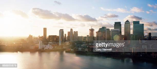 panoramic view of london canary wharf skyline at sunset - london docklands stock pictures, royalty-free photos & images