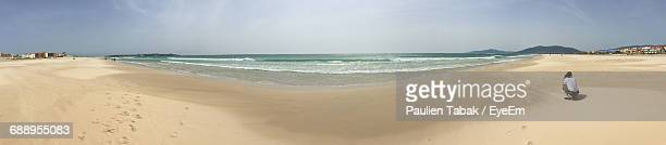 panoramic view of man crouching at beach against sky - paulien tabak stock pictures, royalty-free photos & images