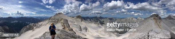 Panoramic View Of Man On Landscape Against Cloudy Sky