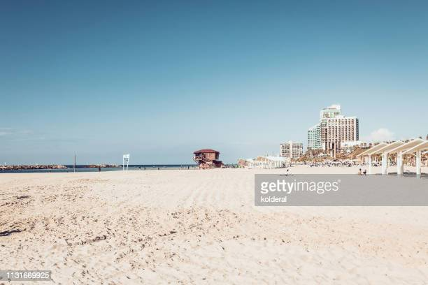 panoramic view of mediterranean beach at midday against blue sky - midday stock pictures, royalty-free photos & images