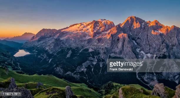 Panoramic view of mountainous dolomiti landscape around Fedaia Lake, Lago di Fedaia, and the summit of Marmolata, Marmolada at sunrise, from a hill...