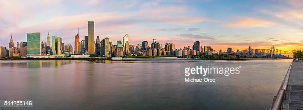 A panoramic view of NYC skyline and the East River during sunrise. Viewed from Gantry Plaza, Long Island City. New York.