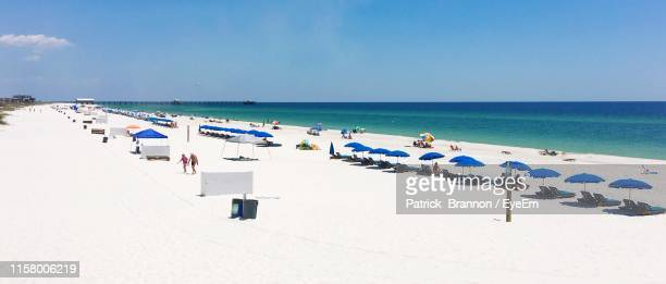 panoramic view of people at beach against blue sky during summer - gulf shores - fotografias e filmes do acervo