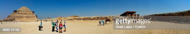Panoramic View Of People At Desert Against Clear Blue Sky