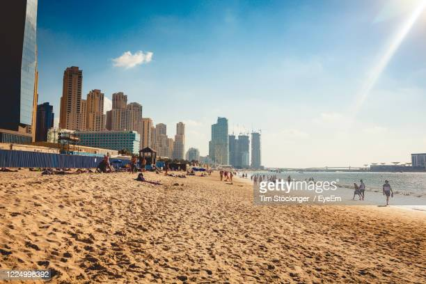 panoramic view of people on beach against sky - dubai strand stock-fotos und bilder