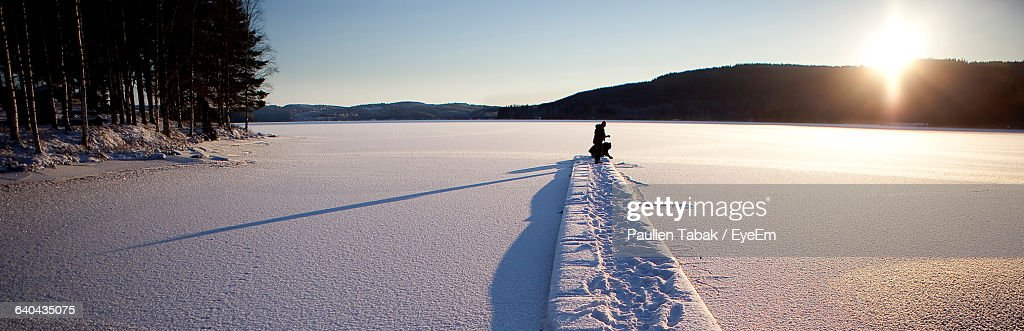 Panoramic View Of People On Jetty Over Frozen Lake Against Sky : Stockfoto