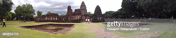 Panoramic View Of Prasat Hin Phimai By Trees On Grassy Field Against Cloudy Sky