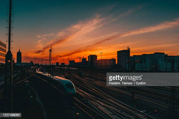 panoramic view of railroad tracks by buildings against sky during sunset - munich germany stock pictures, royalty-free photos & images