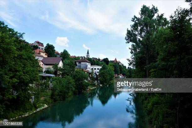 panoramic view of river amidst buildings and trees against sky - kranj stock pictures, royalty-free photos & images
