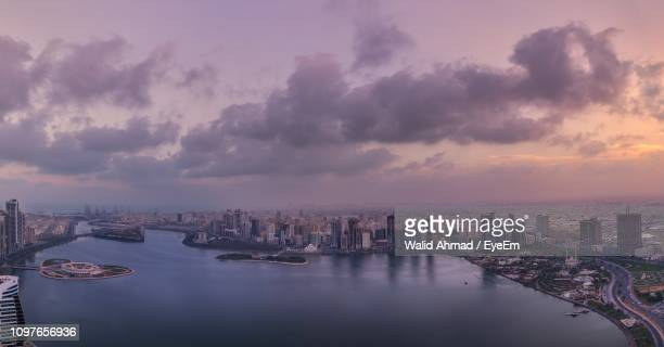 panoramic view of river and buildings against sky at sunset - emirate of sharjah stock pictures, royalty-free photos & images