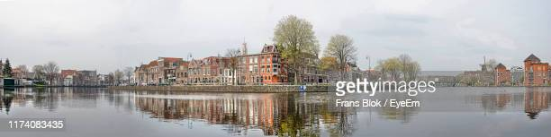 panoramic view of river by buildings against sky - haarlem fotografías e imágenes de stock
