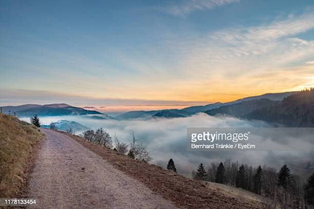 panoramic view of road against sky during sunset - schwarzwald stock-fotos und bilder