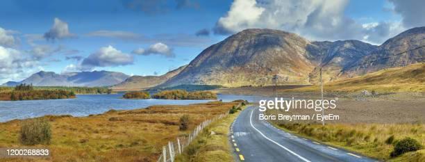 panoramic view of road by mountains against sky - boris stock pictures, royalty-free photos & images