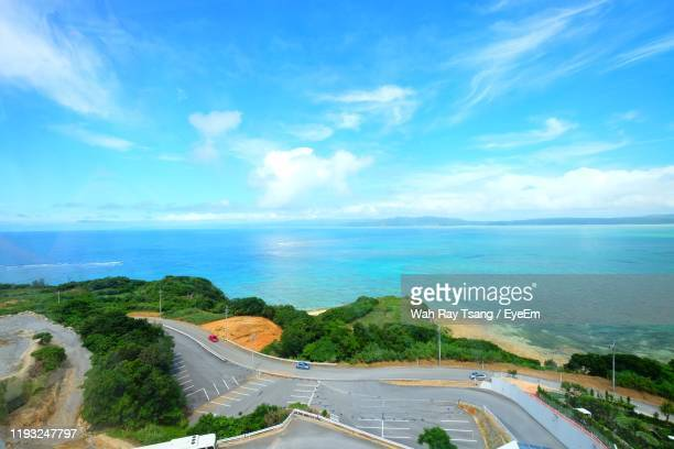 panoramic view of road by sea against sky - 沖縄県 ストックフォトと画像
