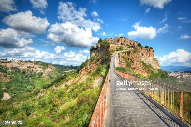 panoramic view of road leading towards mountains against sky - civita di bagnoregio foto e immagini stock