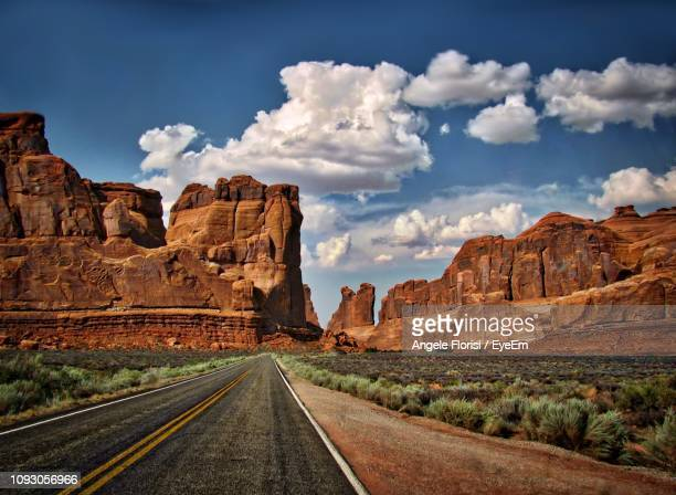 panoramic view of road leading towards mountains against sky - angele florisi stock pictures, royalty-free photos & images