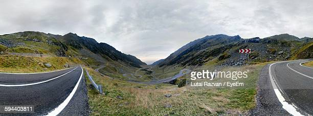 panoramic view of roads on mountains against cloudy sky - lutai razvan stock pictures, royalty-free photos & images