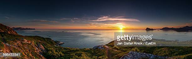 Panoramic View Of Rock Formations By Sea Against Sky During Sunset