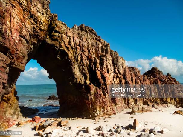 panoramic view of rocks on beach against sky - rock formation stock pictures, royalty-free photos & images