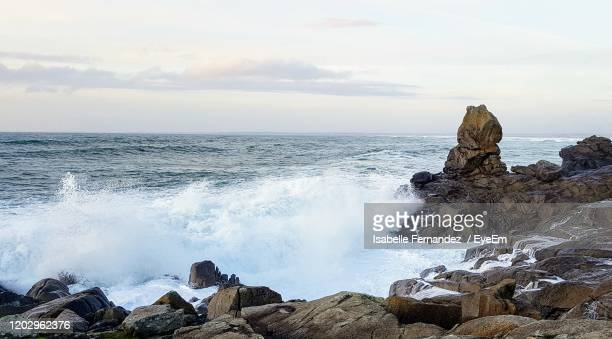 panoramic view of rocks on beach against sky - france strike stock pictures, royalty-free photos & images