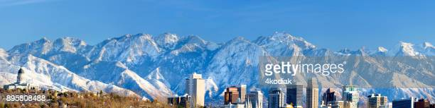 panoramic view of salt lake city with snow capped mountain - salt lake city utah stock photos and pictures
