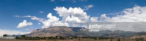 panoramic view of sandia mountains with blue sky and clouds - sandia mountains stock pictures, royalty-free photos & images