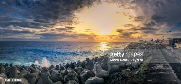 panoramic view of sea against sky during sunset - 防波堤 ストックフォトと画像