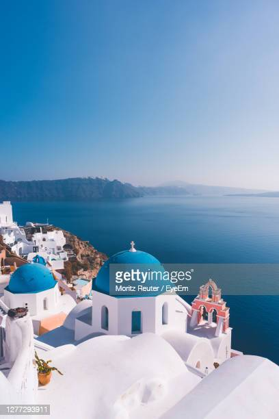 panoramic view of sea and buildings against blue sky - greece stock pictures, royalty-free photos & images