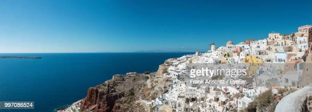 panoramic view of sea and buildings against clear blue sky - athens greece stock pictures, royalty-free photos & images