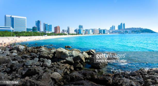 panoramic view of sea and buildings against clear sky - busan stock pictures, royalty-free photos & images