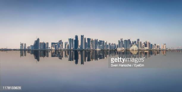 panoramic view of sea and buildings against clear sky - doha stock pictures, royalty-free photos & images