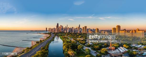 panoramic view of sea and buildings against sky during sunset - chicago illinois stock pictures, royalty-free photos & images