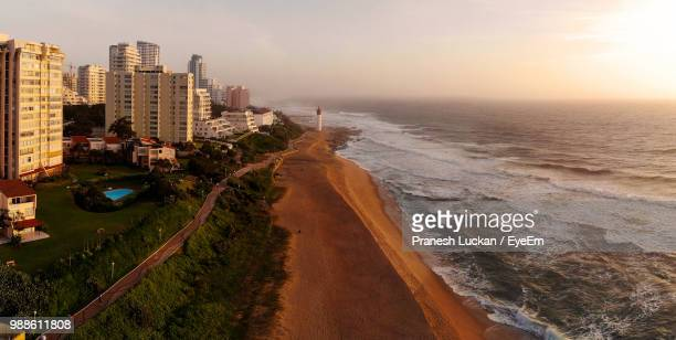 panoramic view of sea and buildings against sky during sunset - durban beach stock photos and pictures