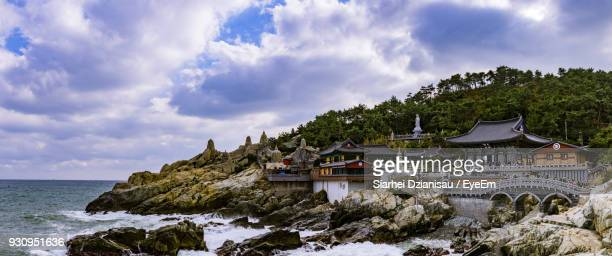 panoramic view of sea and mountains against sky - busan stock photos and pictures