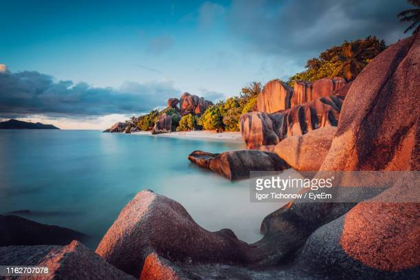 panoramic view of sea and rock formation against sky - seychelles stock pictures, royalty-free photos & images