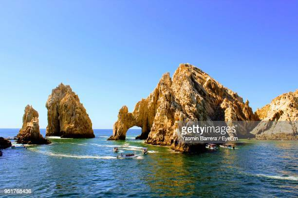 panoramic view of sea and rocks against clear blue sky - cabo san lucas stock pictures, royalty-free photos & images