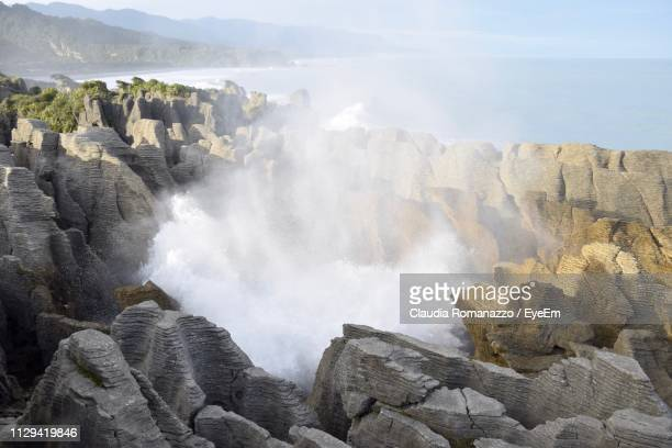panoramic view of sea and rocks against sky - claudia romanazzo foto e immagini stock