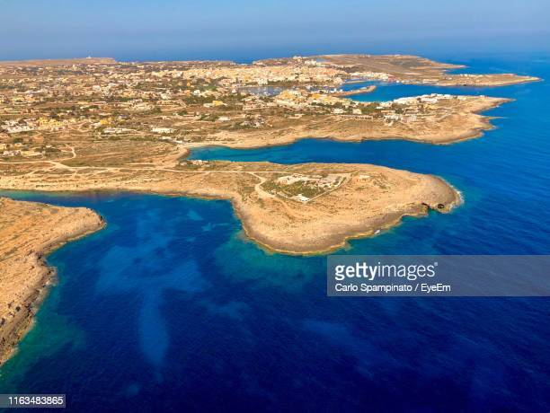 panoramic view of sea and rocks against sky - lampedusa stock pictures, royalty-free photos & images