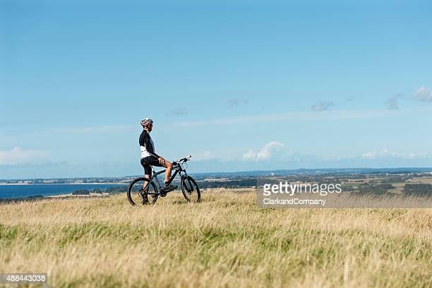 Panoramic View of Senior Man Mountain Biking In Denmark