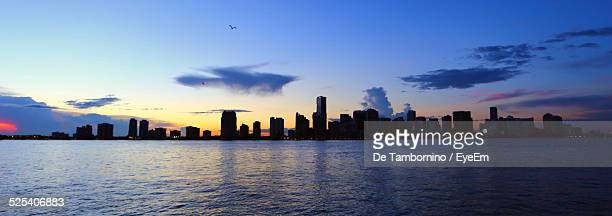 Panoramic View Of Silhouette City Skyline By Sea Against Sky