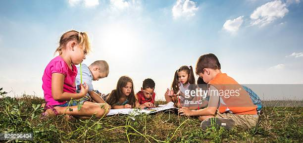 Panoramic view of small kids drawing in a meadow.