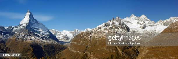 panoramic view of snowcapped mountains against clear sky - donker stock pictures, royalty-free photos & images